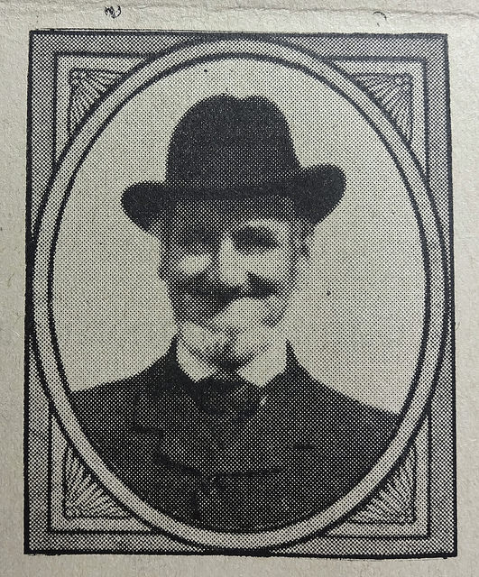 A black-and-white photo showing a smiling man with a white beard, wearing a soft-crowned hat and a dark suit.