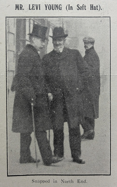 "A black-and-white photo showing three men, one in a top hat, one in a soft-crowned hat, and one in a flat cap.  The man in the soft hat is smiling at the camera.  Text above reads ""Mr. Levi Young (In Soft Hat)."", and text below reads ""Snapped in North End."""
