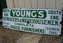 "A long enamelled sign resting on the ground against a wall.  The text is green on a white background, and reads: ""Young's / North End.  South End.  Removers & Warehousemen.  Complete House Furnishers.  Estabd 1864.  Estimates Free."""