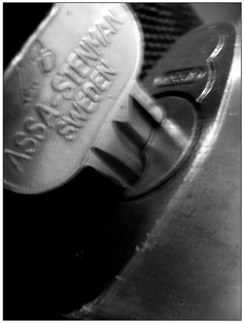 "A blurry black-and-white close-up of a key in a lock. The words ""Assa-Stenman Sweden"" are embossed on the head of the key."