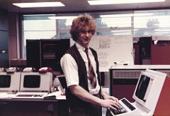 A white person in masculine clothing (checked tie, short-sleeved white collared shirt, brown waistcoat) looking towards the camera in a room full of computer terminals.  Their hands are on the keyboard of one of the terminals.  Daylight and the chimneys of another building are visible through a window behind.