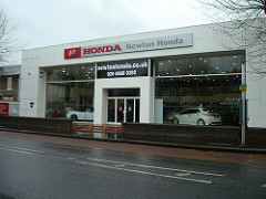 "A large, white, blocky building with large plate-glass windows showing cars parked inside.  A sign above the windows reads ""HONDA / Newton Honda""."