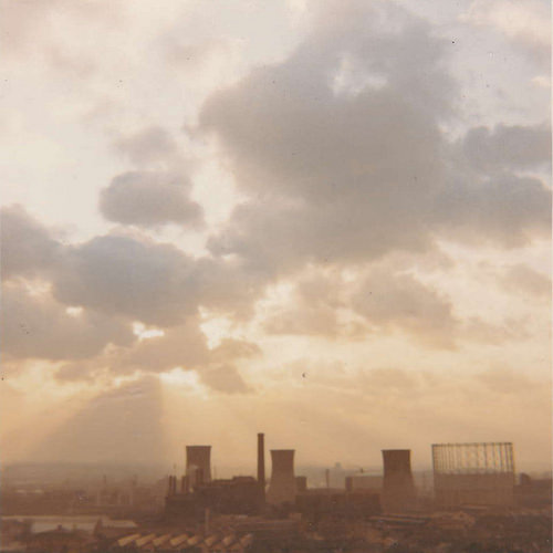 A hazy photo showing the sun behind clouds with power station cooling towers and a gasholder below.
