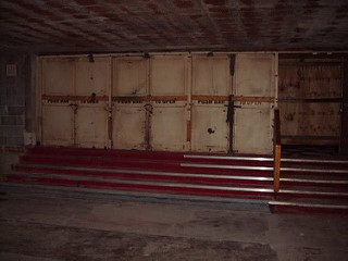 A wide set of four red-carpeted steps leading up to unpainted doors, below a low ceiling above an unfinished floor.