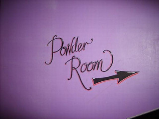 "A pinkish-purple wall with the words ""Powder Room"" painted on in black cursive.  Below is an arrow pointing slightly upwards."