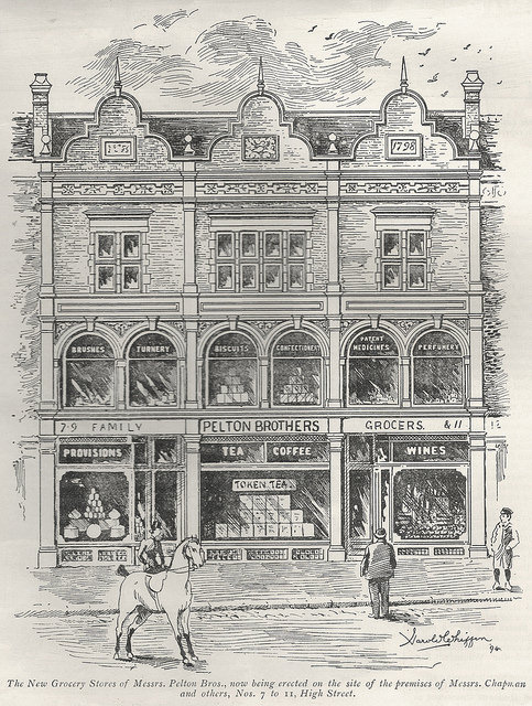 "Drawing of a three-storey, three-shopfront building with ""1798"" on a plaque at the top and signs in the windows underneath advertising brushes, turnery, biscuits, confectionery, patent medicines, perfumery, provisions, tea, coffee, and wines."