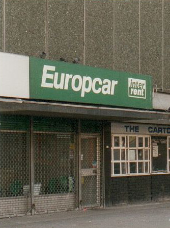 "A small shopfront with a green and white ""Europcar / inter rent"" sign above.  The shopfront itself is covered with a metal mesh shutter.  It's unclear whether the shop has closed down or is merely not open at the time of photography."