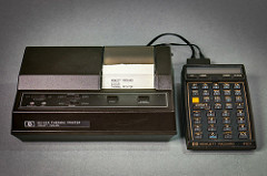 "Two pieces of 1980s-looking hardware with black plastic cases, connected together with thin black cables.  The one on the left is larger, and has a narrow piece of paper coming out of it with ""Hewlett Packard / 821621A / Thermal Printer"" printed on it in all-caps, and the one on the left has a blank one-row display above several rows of buttons labelled with letters, numbers, and abbreviations of mathematical functions such as sine, cosine, and tangent."