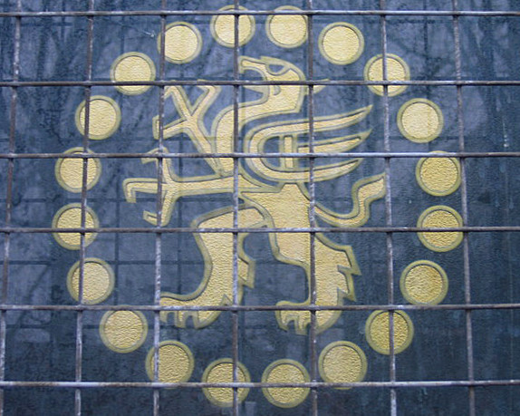 A circular logo embossed on a window behind a thin grille.  In the centre is a stylised griffin, surrounded by a circle of smaller circles (representing coins).