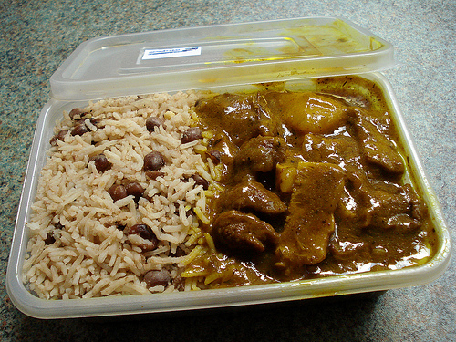 A rectangular plastic takeaway tub with rice & peas in the left side and curry goat in the right.
