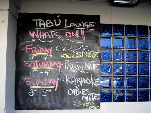 "A blackboard with chalked writing in red, yellow, and white: ""Tabú Lounge / Whats On!! / Friday 11pm–4am Chocolate Royale Afrobeats & R&B / Saturday 11pm–4am Party Nite Revival / Sunday 8pm–3am Karaoke & Oldies Nite 70's & 80's Disco"".  The dark blue tiling mentioned earlier is visible to the side."