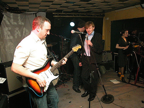 Four white people on stage in a low-roofed venue.  One is playing a guitar, one is holding a microphone, one is playing a keyboard, and one is turned away from the camera and partly obscured by the microphone-holder.