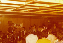 A yellow-tinged photo of five young white people playing on stage in a low-ceilinged room with an audience crowded up together in front of the stage.