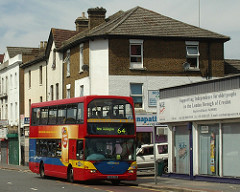 "A double-decker red bus with the blind showing ""New Addington 64"".  Behind the bus can be seen a corner shopfront with a sign reading ""G[...]napat[...]""."