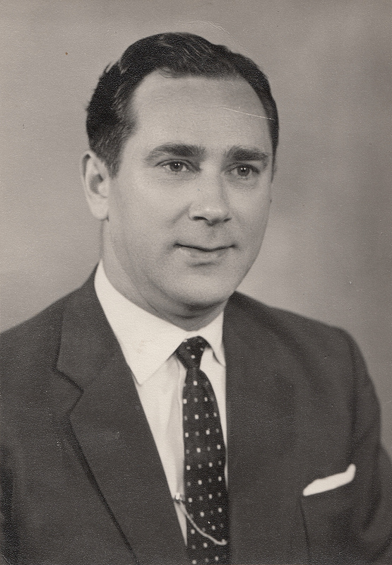 Monochrome photo of a white man with neat dark hair and a wistful look, wearing a dark suit with white pocket square, white shirt, and dark tie patterned with small white dots.