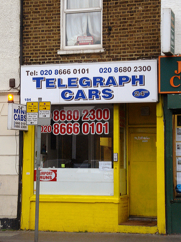 "A small terraced shopfront painted in mustard yellow, with a large white sign above reading ""Telegraph Cars"".  Two phone numbers are shown prominently in the front window.  There is a recessed door to the right, again painted mustard yellow, and an intercom on the front of the shop next to it."
