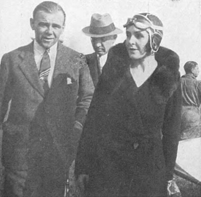 A black-and-white photo of two people (with another behind them, mostly obscured) standing or walking towards the camera.  The one on the left is wearing a suit with a tie and buttoned-up jacked, and the one on the right is wearing a fur coat and aviator's cap and goggles.
