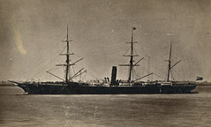 A sepia-toned monochrome photo of a ship at sea, with three tall masts and a smokestack.