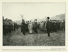 A side-on view of men in bowler hats and dark coats standing in long lines in a field.  A short man in a military hat and with a long pale double-breasted coat is walking between one of the lines towards the camera, followed by at least two more bowler-hatted men.