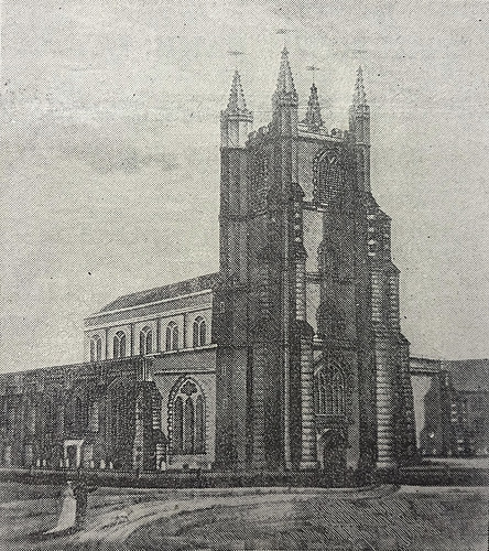 A church building with a large square tower at one end.  Two people, one in a white dress and one in a dark suit, are standing on the path that leads up to the entrance.