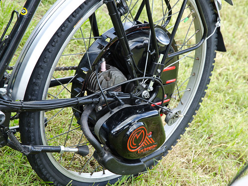 A close-up on a bicycle wheel with a black motor at the hub.  The bicycle is standing on grass.