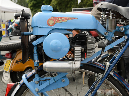 A small engine in a pale-blue casing, mounted on top of a bicycle wheel.  A couple of what look like motorised scooters are in the background.