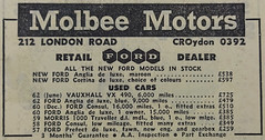 "A newspaper advert headed ""Molbee Motors"", listing several cars for sale including a new Ford Anglia at £538 and used cars ranging in price from £259 for a 1957 Ford Prefect to £725 for a 1962 Vauxhall VX."