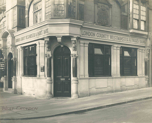 "A black-and-white photo of a ground-floor end-of terrace property with an arched doorway at the corner and large rectangular windows along both sides.  An embossed sign running above the windows reads ""London County Westminster & Parr's Bank"".  ""West Croydon"" has been handwritten in the lower left corner of the photo."