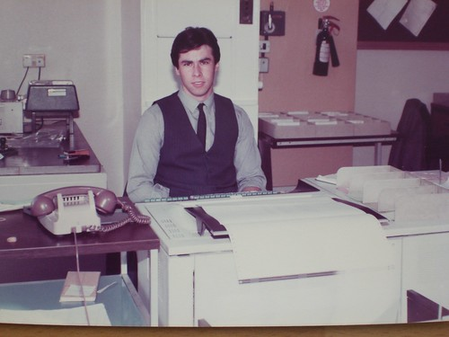 A young white man wearing a light-blue shirt with dark tie and waistcoat, sitting behind some sort of computer-style machine with a keyboard and printout slot.  An old-fashioned telephone with handset and spiral cord is on a desk to one side, and index-card boxes are visible in the background.