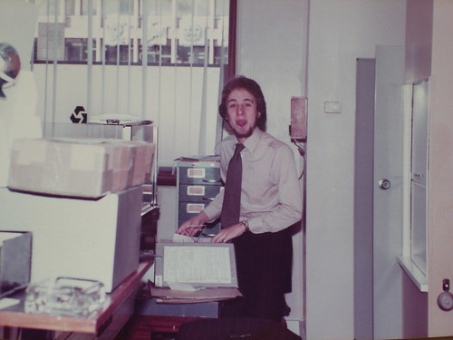 A different young white man wearing a light-brown shirt with a dark patterned tie.  He is standing at the side of a desk with some files and folders on top of it, and poking his tongue out at the camera.  A card index cabinet is behind him, and beyond that is a window with open blinds, through which the mouldings of the Zodiac Court frontage are just visible.