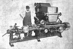 A black-and-white photo of a person with an impressive moustache, wearing a cap and dungarees and standing with one hand on their hip behind a long machine which seems to involve quite a lot of rollers.