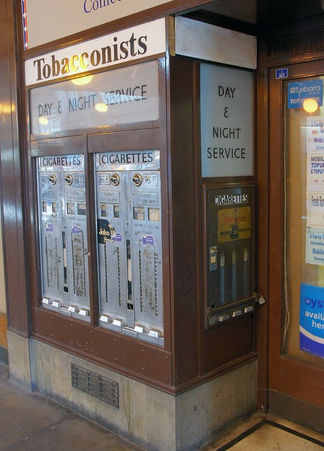 "Three old-fashioned vending machines inlaid into two sides of a protruding wall.  A sign at the top reads ""Tobacconists"", and others just below this read ""Day & Night Service"" and ""Cigarettes"".  The machines themselves are plain metal, flush with the wall, and have coin slots at the tops.  Partially-removed stickers and plaques advertise John Player Special and Benson & Hedges cigarettes."