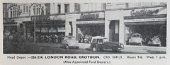 "A low-resolution newspaper photo of an extensive shop frontage spanning five individual shop premises and three recessed entrances to the flats above.  The fronts of the shops have been opened up to display cars and motorbikes inside.  Signs above read ""Godfreys"".  Text underneath the photo reads: ""Head Depot:— 226/234, London Road, Croydon.  CRO. 3641/3.  Hours 9–6.  Wed. 1 p.m.  (Also Appointed Ford Dealers.)"