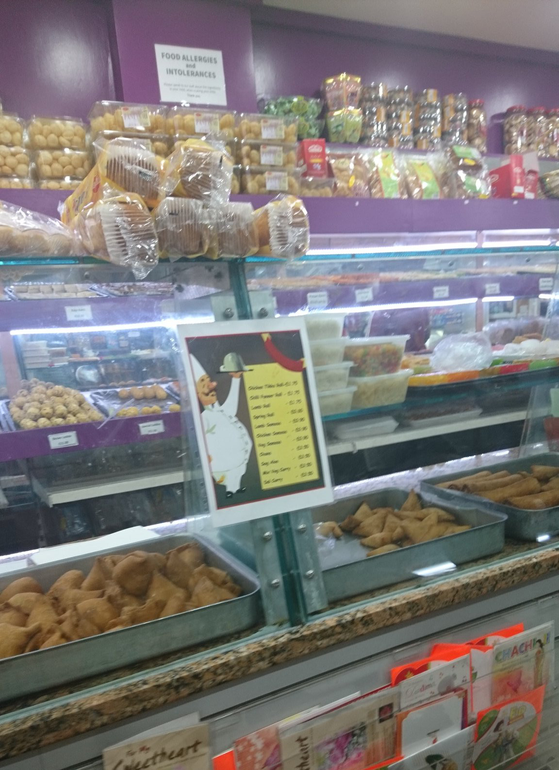 A glass-fronted display counter with trays of samosas.  Behind are shelves lined with Indian sweets.