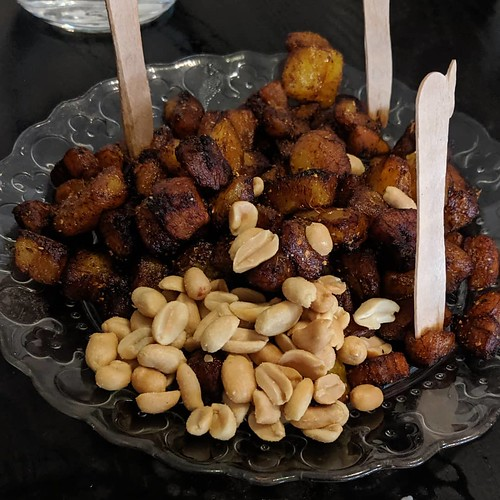A clear patterned plate piled with dark brown cubes of plantain and a handful of roasted peanuts.  Small wooden forks are stuck upright in the pile.