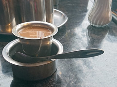 A metal cup of milky tea in a tall metal saucer.
