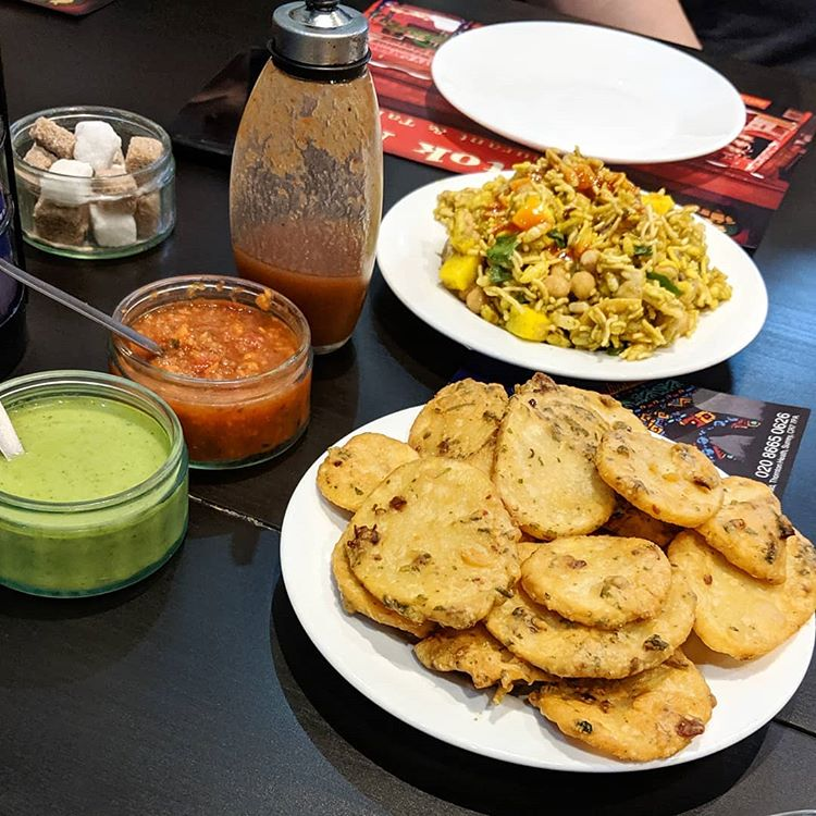 A plate of thin oval fritters in the foreground, with another plate of mixed puffed rice, chickpeas, and cubed potatoes behind.  Small glass dishes on the side hold red and green sauces.