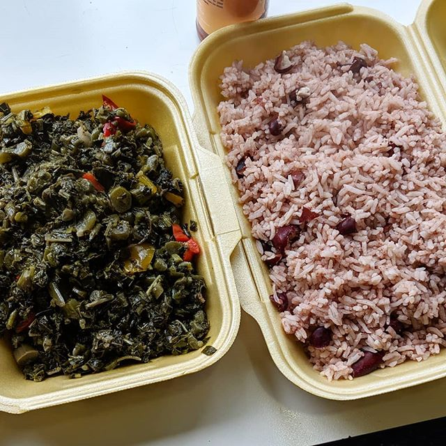 Styrofoam takeaway containers on a table.  One is filled with dark leafy greens cooked down with red chillies and onions, and the other with pink-tinged long-grain rice cooked with kidney beans.